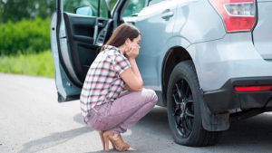 a woman driver has a flat tire