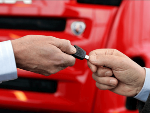 two hands hold a car key on a red car background
